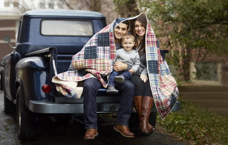 young family on bed of truck in rain